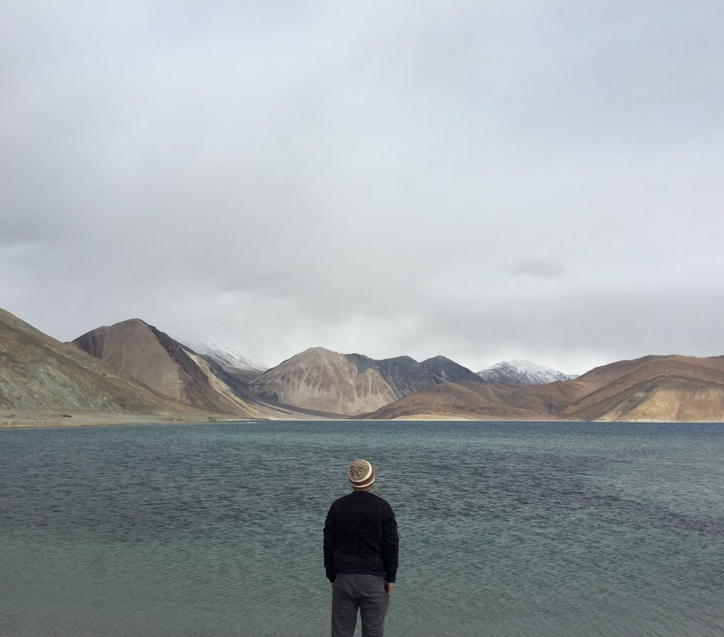 Man Traveler standing alone on cliff lake and foggy mountains on background Travel Lifestyle inspiring concept outdoor