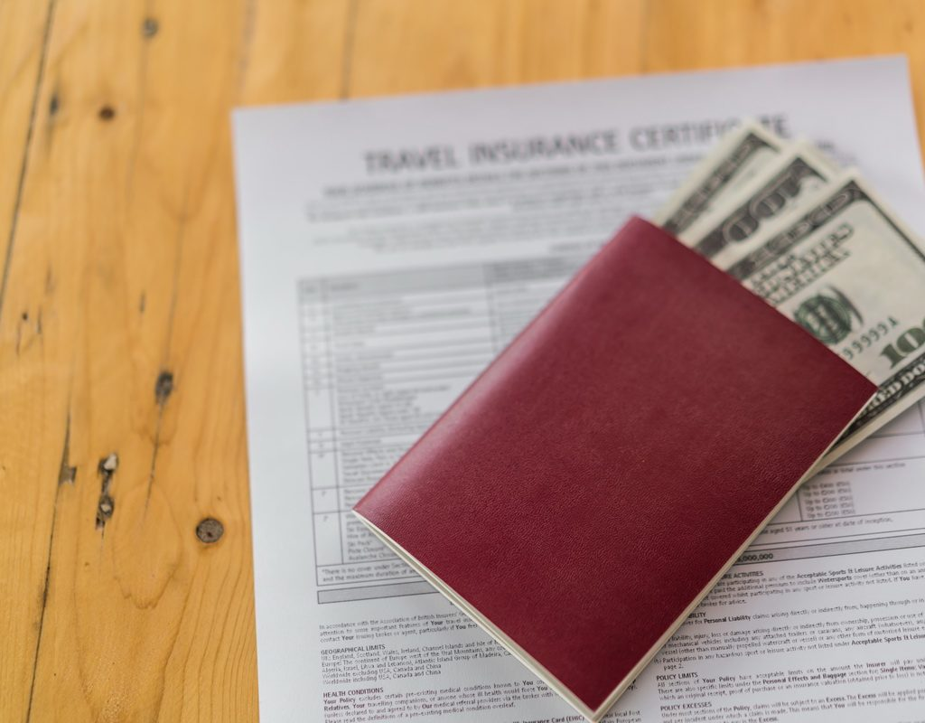 Blank passport with US dollars on wood table over Travel Aviation Insurance application form
