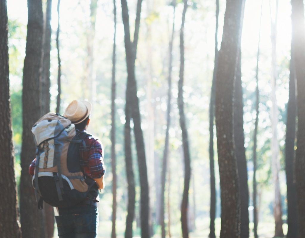 Blur image of Young Man Traveler with backpack relaxing outdoor. Relax adventure and lifestyle hiking travel idea concept. Vintage retro film effect.