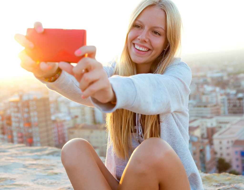 Outdoor portrait of beautiful blonde girl taking a selfie on the roof.